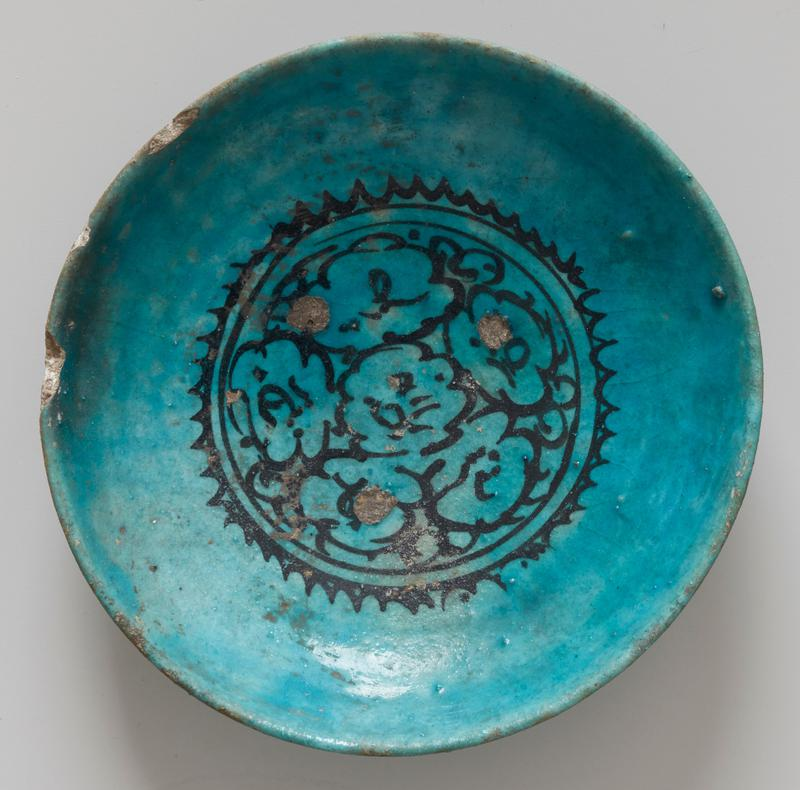 Blue plate or shallow bowl of green-blue semi-opaque glaze with a floral design painted in black outline in the bottom.
