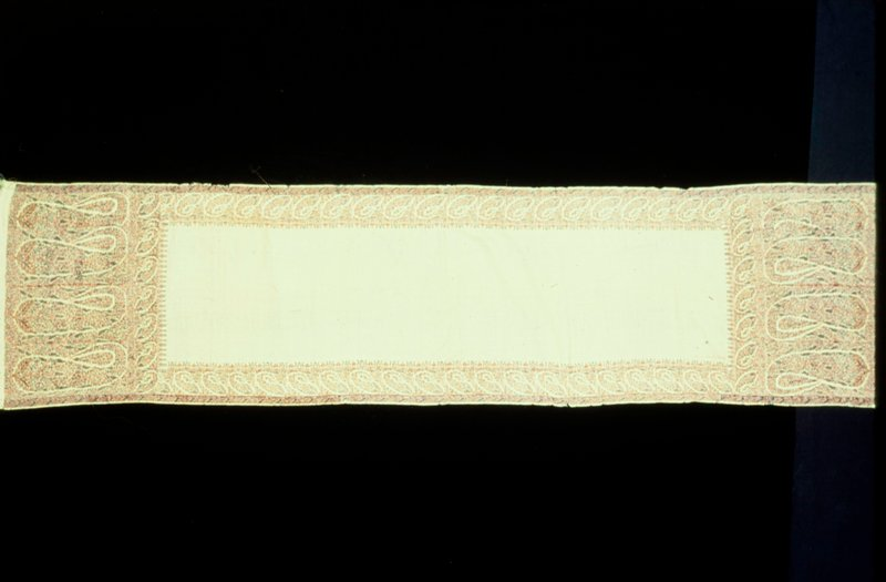 Doshalla or long shawl bearing a maker's signature in corner; white wool ground with borders, wide at ends and narrow along sides of Buthas or cone-shaped ornaments with floral network separating borders woven separately and joined to shawl.