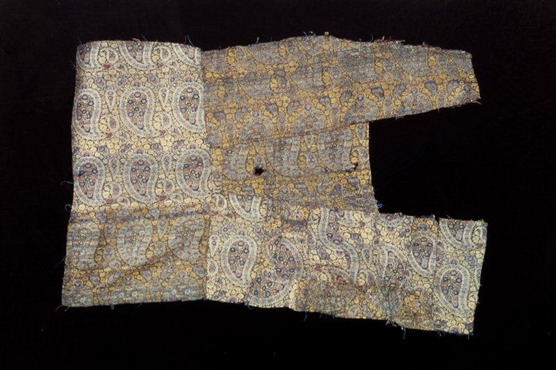 Irregular fragments of brocade sewed together, possibly part of a costume. Patterned with large and small palmettes and yellow flowers on a dull blue ground.
