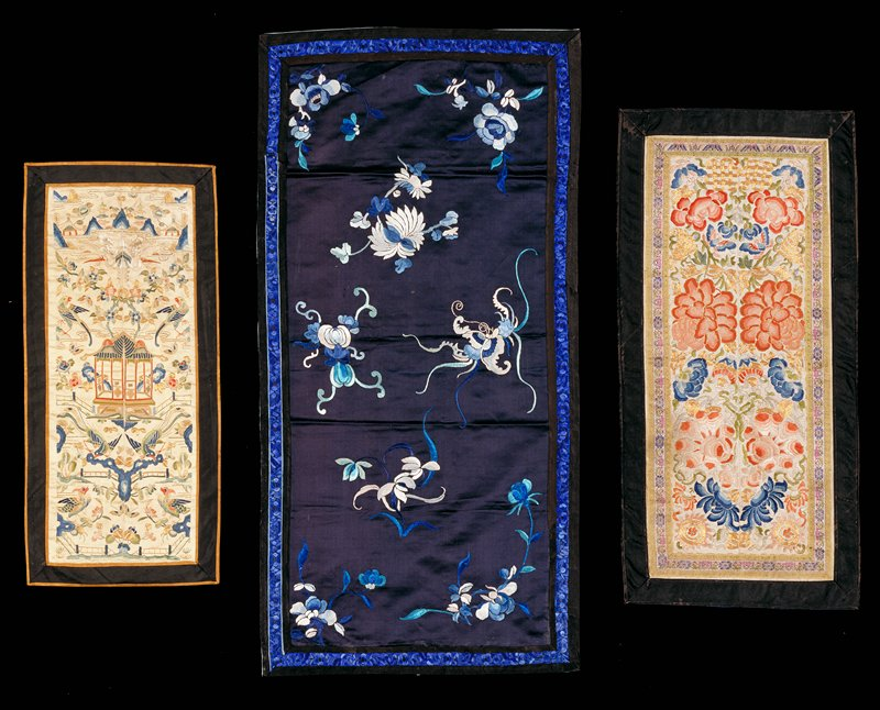Black satin cover embroidered with flowers and butterflies in shades of blue. Finished with a narrow embroidered border of blue flowers and lined with blue cotton.