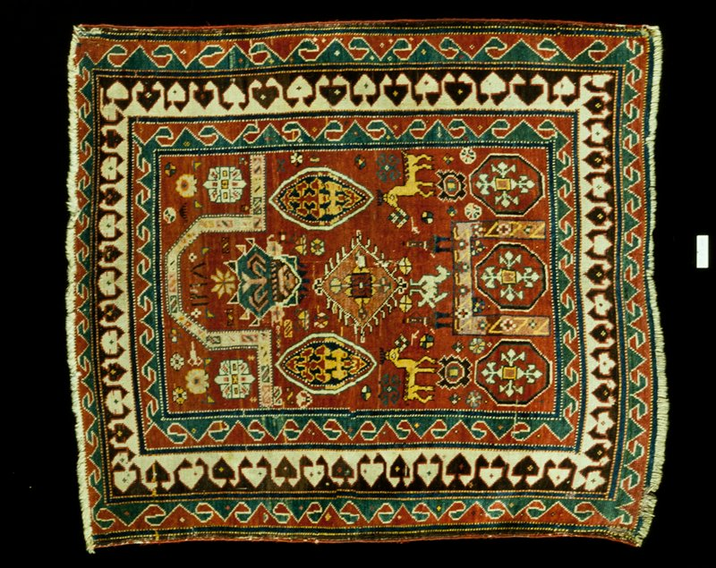 Prayer rug of Kazak type., Typical prayer arch, formed by narrow, ivory bands, which extend transdversely at each side to the borders. At the bottom of the field is a second, square arch. Light red field, scattered with geometric and conventionalized flower forms. Three borders carrying variations of the reciprocal clover leaf design. Sides finished with red woolen cording. Ends worn, ends in short warp fringe. Ghiordes knot. Woolen warp and woof.
