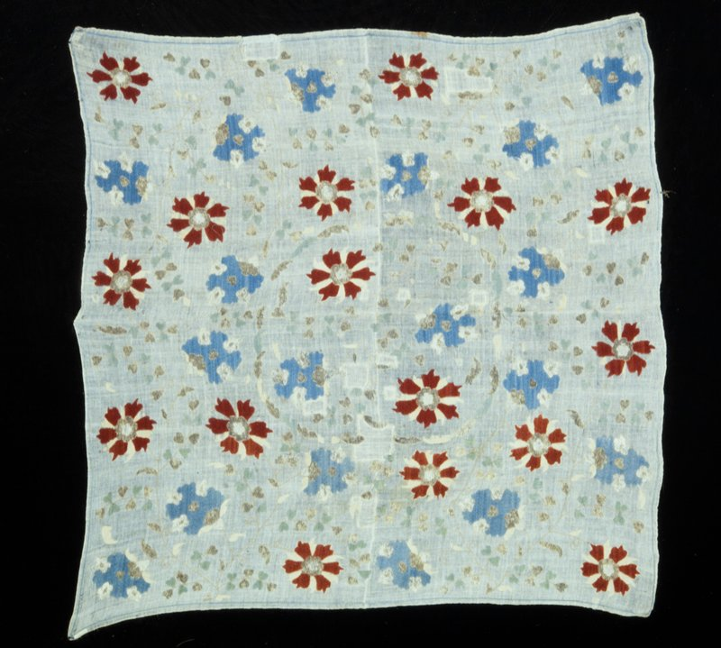 Cover of loosely woven linen material embroidered in silk and metal thread with leaves and flowers. A band of leaves forms the center medallion . Blue and henna are the predominating colors. Linen.