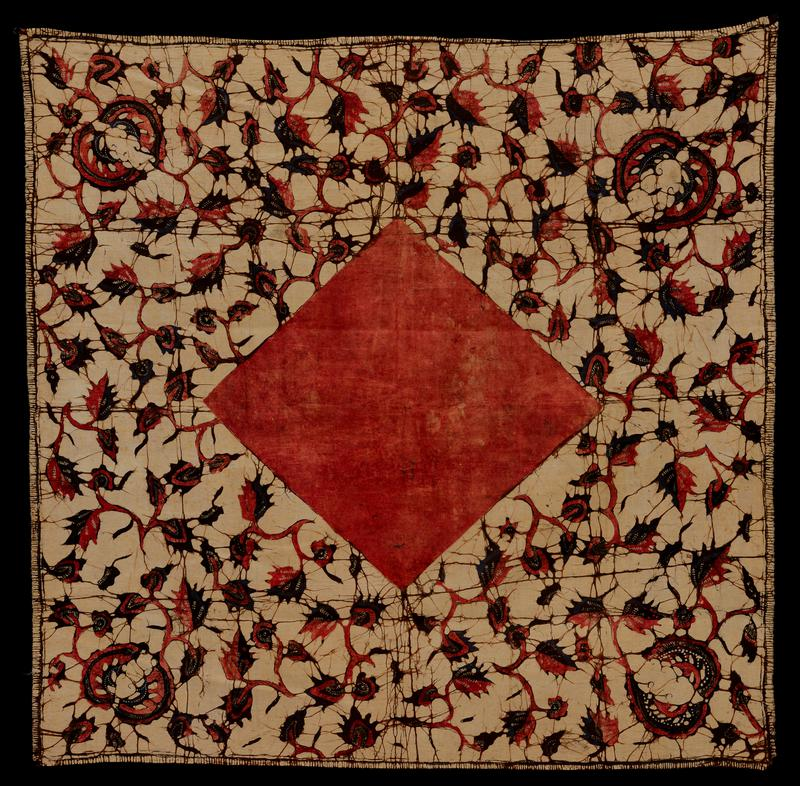 Square, batik, printed. Leaf and vine design in dull red, dark blue and black on tan ground. Square center of dull red.