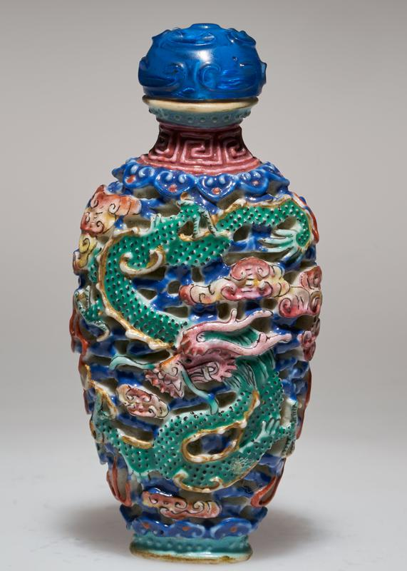 Snuff bottle, colored reticulate porcelain. Cover of blue stone fitted with ivory spoon. Conventional design of three-clawed dragon and phoenix in clouds.