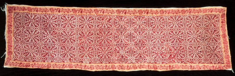 Strip of tan linen composed of two pieces joined horizontally. Embroidered in all-over lozenge stitch. The 2.5 inch border, of red and gold brocade in flower desing, is complete.
