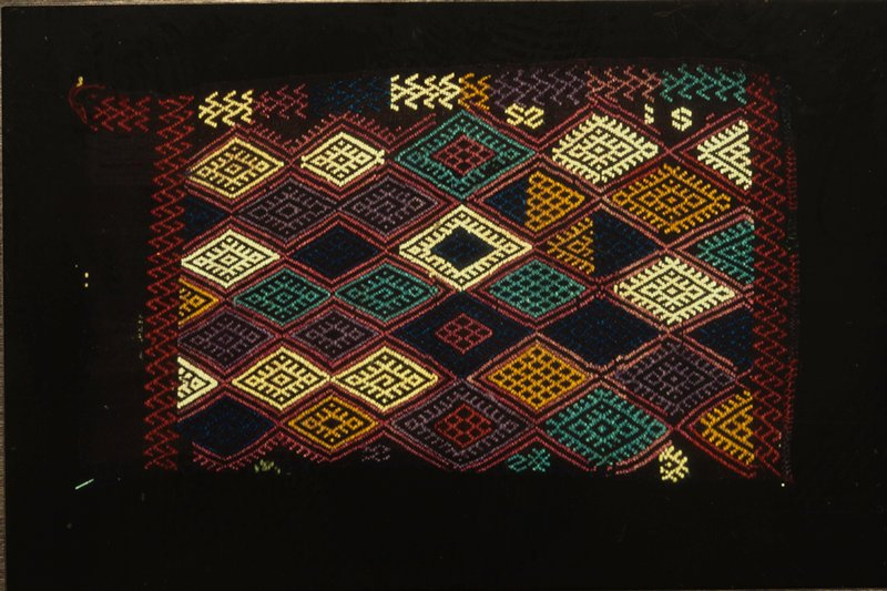 31.81.12-15 Camel bags, portion of. Black woolen strip embroidered in lozenge design in yellow, blue, red and green. This is probably nomad work. Wool.