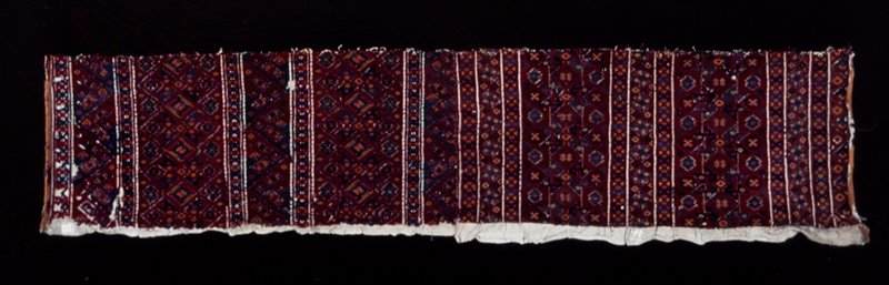 Tent hanging, strip of, embroidered in shades of rust red, blue and green, in stripes, one wide strip alternating with a broad one. The design is geometrical and so closely embroidered that it looks woven. Probably Kurdish. Embroidery.