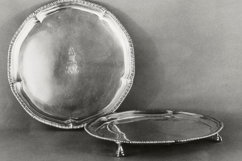 salver, pair of; lobed circular tray on three claw and ball feet; rim molded and chased with gadroon ornament; center engraved with a monogram consisting of the letters below a flaming urn crest standing for John and Cornelius Glen Van Rensselaer, in whose family they were until 1932
