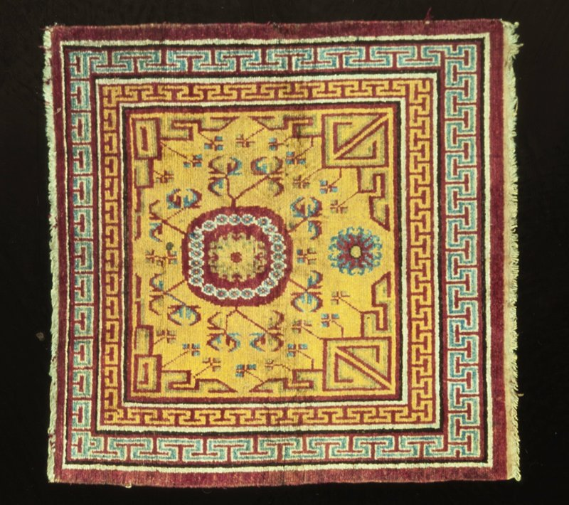 Mat, Samarkand type, small, with one large floral medallion in center and a smaller one below it. Gold field scattered with flowers in profile and stiff vines. Three borders, the outer one plain red, the inner ones carrying the Greek meander on red grounds. Two guard stripes, one black and one pale blue separate the borders. Side sovercast in red wool; one end finished with short web and twisted warp fringe. The other has a short fringe of warp threads. Warp cotton; woof cotton. Senna knot.