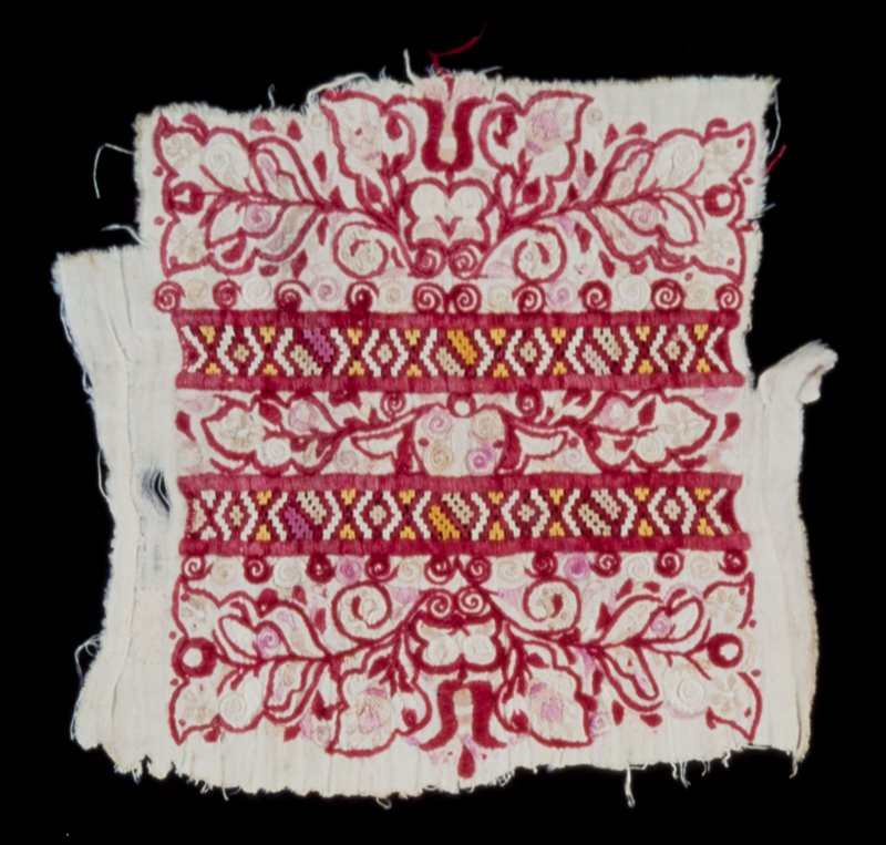one of a pair of pieces from dress, embroidered in several colors, chiefly red; floral, foliate and scroll designs; two borders of conventional openwork divide the embroidery into three sections; the center one, a narrow band