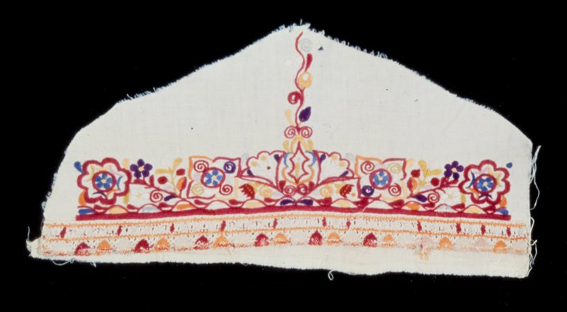 piece from sleeve embroidered with flower designs in several colors, principally red; a band of colored lace on the hem