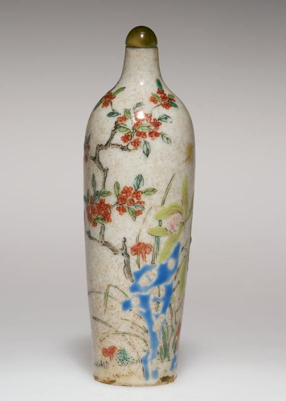 Snuff bottle, painted white porcelain, with stopper and stand. Design of fruit blossom in red and yellow; minute brownish specks under the glaze give the white porcelain a beige cast.