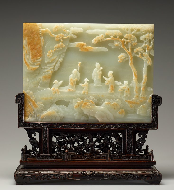 Table screen, white jade covered with brown skin matrix carved in relief with a scene depicting the meeting of Laozi and Hon fu Tsu in a mountainous landscape with pine trees. On the reverse side a carved swastika design on a plain ground.