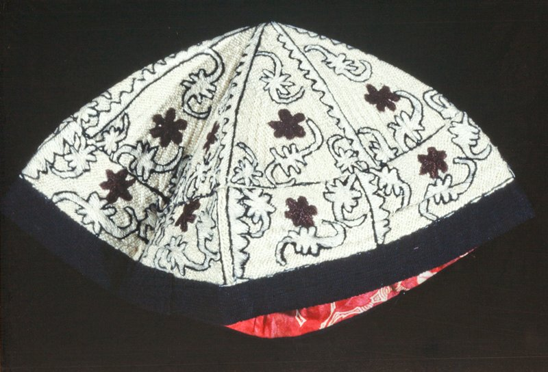 skull cap, folding into six sections, worked in white silk over cords into all-over design, further ornamented with 6 lobed stars in brown and cuving frond-like designs in white outlined in brown; edging of black braid; partly lined with red and white calico