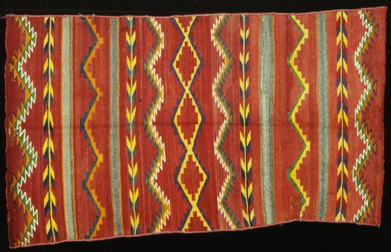 rug, Navajo, red ground with design of horizontal bands carrying designs of deep zigzag stripes, a conventionalized floral vine, step-sided lozenges, and stepped pyramids in red, yellow, purple, green, orange, black and white; sides burttonholed in red yarn