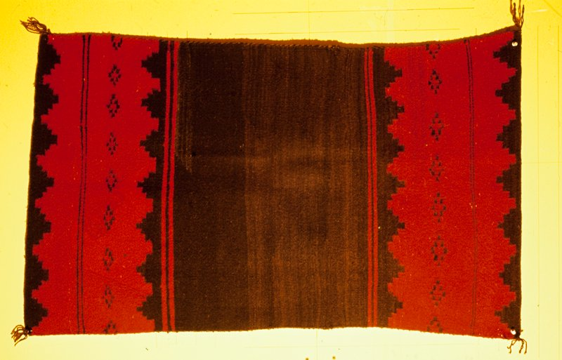 rug, Navajo, black with wide end borders of red edged with stepped designs in black and carrying a band of broken lozenge motifs in center; this is said to be half of a dress worn by the Navajo Indians