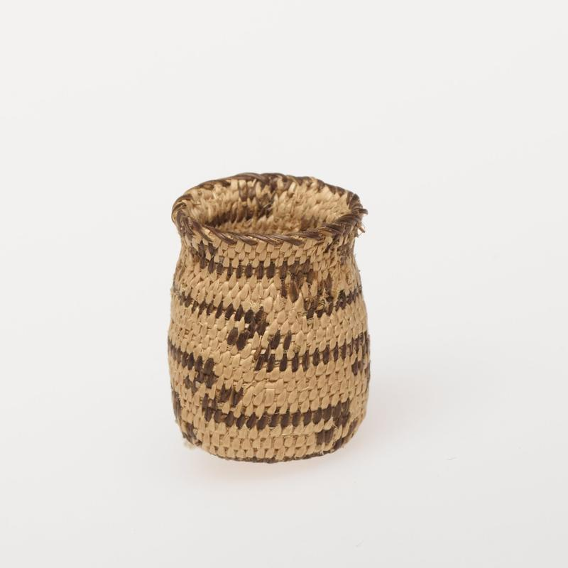 Miniature round basket with cover; coiled. Design consists of a stepped radial pattern of coyote tracks and horizontal stripes. Colors are natural and black.