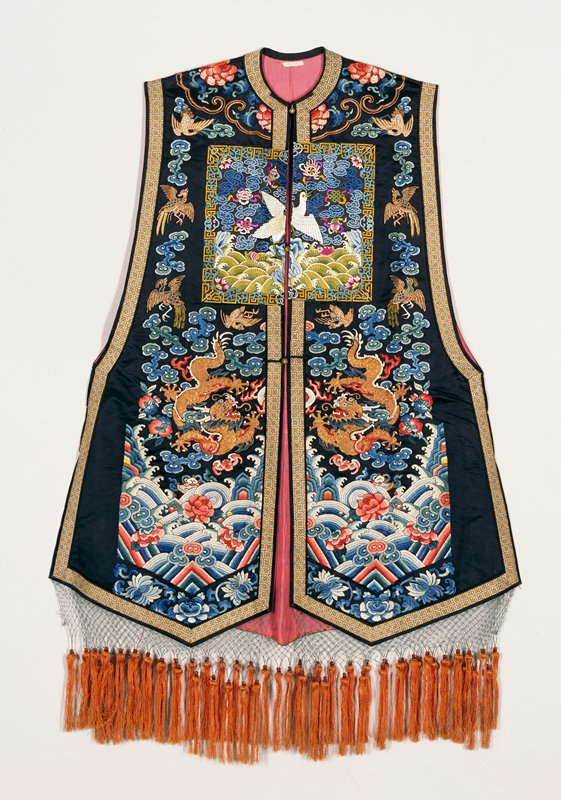Sleeveless coat of blue-black satin embroidered in satin, knot, couched, and outline stitch in shades of blue, green, yellow, red, purple, cerise, olive-green. Three 5-clased dragons in gold. Applied on breast and in middle back a mandarin square with a crane and Buddhist symbols, indicating rank of the wearer's husband. Body of coat has clouds, double-peach, phoenix, and bats. Conventional border, but with stripes barely visible. Rolling waves scattered with blossoms and symbols. Border of yellow and silver brocade. Collar band simulated by couched gold thread. Lining of thin pink silk. Fringed bottom.