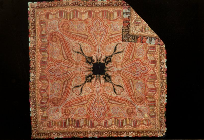 Square shawl, of hand-loom patchwork with a design of large scrolls and serpentine border. The outer border is embroidered on strips of plain colored wool. Colors chiefly red, yellow, blue, green; lining of black cotton. Badly worn and darned in middle field. One corner turned back on field and stitched down. #13 in travelling exhibition.