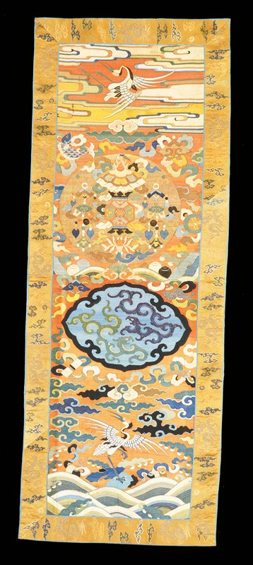 Chair cover of brick-red k'ossu that has faded in exposed areas. In the top section, in a loose cloud field, a white crane. Just below, a medallion of gold k'ossu with lotus flower and various symbols. In the surrounding field are Buddhist symbols. Colors include shades of blue, green, pink, tan, yellow and red. In the lower section, in a shaped medallion, two dragons of K'ang Hsi type in green and dark blue on a medium blue ground. Below, in a cloud field, a white crane and good luck symbols. At the bottom, the waves of the Eternal Sea. Colors include shades of blue, green, yellow, brown, black. Note the restored block area of clouds. Border of tan satin brocaded with dragons and clouds in colors and gold. Bindings of medium blue silk. Lining of gold colored figured silk.