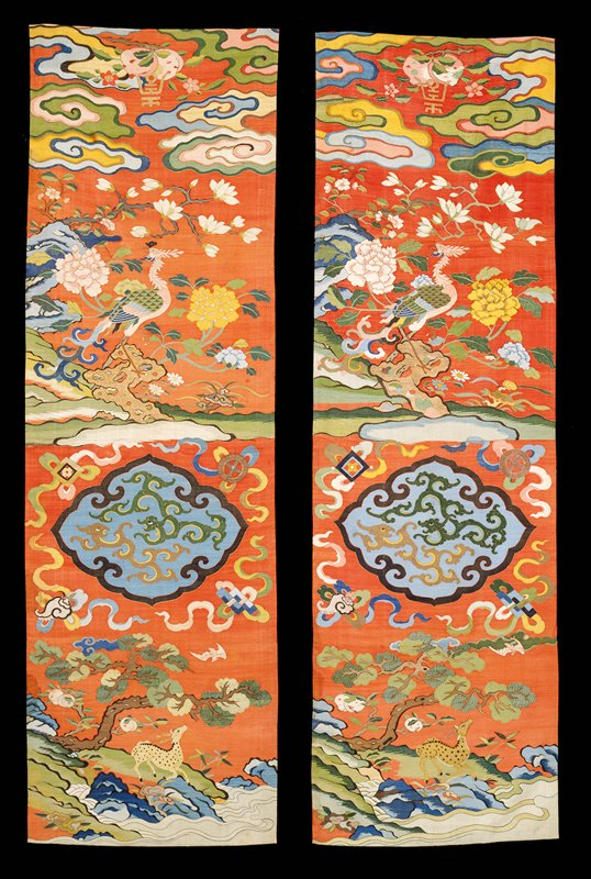 Chair cover of red kesi. In the upper section wide, loose, joining clouds; peaches with the longevity character in gold; magnolia and peony blossoms, and a phoenix in shades of blue, pink, green, yellow and tan. In the lower sectionin a shaped, quatrefoil medallion, slender Kangxi-type dragons in green and tan on a medium blue ground. Below, a spotted deer in a landscape with peaches, fungus, and a branching pine tree. In the field are Buddhist and other symbols. The colors are those of the upper section. Lining of crimson satin.