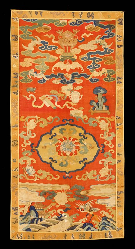 Chair seat cover of red k'ossu with loose clouds, sacred vessels, bats, crane and pagoda in landscape. The central device is a lotus blossom in a quatrefoil medallion. Colors include shades of blue, green, yellow, pink, tan as well as gold threads. Border of tan brocade satin with cloud, dragon, and Heavenly Jewel design in blue, green, tan, and gold threads. Lining of strong yellow satin damask of cloud design. Some painted details in k'ossu, which is worn in places.