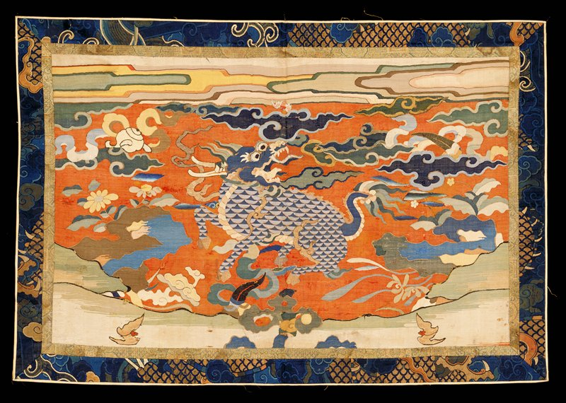 Altar frontal of pale brick red kesi with design representing a blue-scaled chilin in a field of flowers, large fat clouds, and symbols in shades of blue, green, pink, yellow, brown and grey. Across the top a band of watery, run-together clouds.(?) Note the bat, of finer, later kesi inset above cloud over chilin's head. Double border inner one of worn, all-over flower and cloud pattern of brocade in shades of light green, yellow, blue and pink; outer of gold and blue kesi of dragon and cloud pattern, perhaps originally part of a robe? The kesi weave is quite coarse. It has been badly worn, and is mended in places. Lining of yellow satin which has been pieced out.