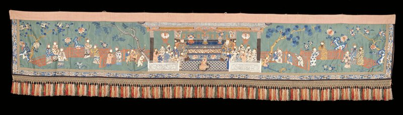 Long valance of embroidered pale jade green satin. The design represents an old man and his wife who are being honored on their birthday by various people. The central design is a temple with sacred objects on the altar. Landscape background with trees, trellis, flowers, etc.;chiefly satin stitch. At bottom and ends a narrow border of white satin embroidered with blossoms and good luck symbols, double swastika, etc., in shades of blue and in gold thread and peacock feathers. Inner border of ivory braid with trefoil design in colors. At the bottom, a strip of vari-colored tassels. Lining of coarse pink cotton.