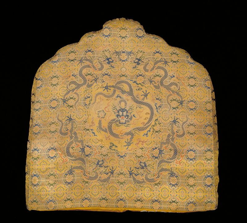 Shaped Throne-back cover of imperial yellow satin brocade. Central medallion with large five-clawed dragon in blue and gold. Surrounding this motif, on a diapered ground of large and small, shaped, flowered medallions, four five-clawed dragons in profile, also in blue and gold threads. Other colors include green, pink, mauve and red. The sides of the cover are deeply boxed to fit cushion. Lining of gold colored damask with large cloud design. Inscription.