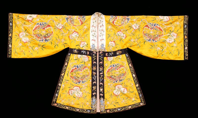 Theatrical robe (for a Taoist immortal) of yellow satin embroidered with large scale design of peaches, bats in medallions, and floral sprays. Collar-band, extending to waist, of embroidered white satin. Cuffs and all-around border of black satin embroidered with running floral pattern. Belt section, stitched at upper edge only, of embroidered black satin, and two narrow hanging panels of the same at each side of front opening. Long, very wide sleeves, chiefly satin and couched stitch. Lining of thin pink silk. Note This robe reputed to have been worn by a Tibetan prince.