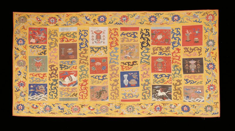 Buddhist priest robe of fine quality kesi woven in squares and strips of different color to represent the rags of Buddha in his mendicant days. Yellow is predominant, with pieces of red, black, gold, green, blue, white, brown, and pale blue. Designs include Buddhist symbols, sacred vessels, cursive profile dragons, loose clouds, chilin, elephant, peonies, phoenix, Foo dog, and imperial five-clawed dragon in shades of blue, red, green, pink, puce, black, olive-green, yellow, and mauve. The border contains a running design of large peonies and leaves. Note some of the weaving done with peacock feathers. Lining of burnt orange damask of large cloud pattern.