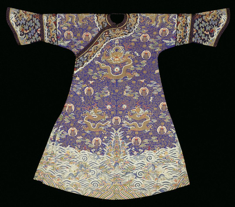 Imperial k'ossu robe of K'ang Hsi (?) blue with all-over tendril pattern of gold in ground, nine five-clawed dragons. Loosely drawn clouds in shades of green, yellow, rose, and aubergine, and spaced motifs of red bats enfolding a gold character with their wings. These are supplemented by bats in yellow, white and rose. Fine border design of rolling waves sprinkled with sprays of flowers, Buddhist and Taoist symbols. From the waves emerge sprags of marcissus, pagodas, etc. Note areas where waves have been painted. Sleeves finished with a band of dark blue k'ossu decorated with universe and dragon motif, above a widely flaring cuff of the same K'ossu. Collar and front band of same k'ossu. Coat slit at sides and lined with yellow raw silk. Inscription inside front.