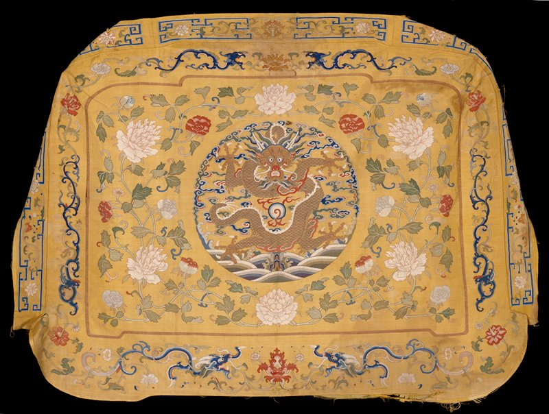 Throne seat cover of imperial yellow k'ossu. In a round, central medallion, a five-clawed dragon in gold is seated above the Eternal Sea. Surrounding him are loose clouds, some of which form the border of upper section of medallion. In the field outside the medallion are large sprays of peonies with twining leaves. In the border, set off fron the main field by a nerrow gold band, are slender, cursive dragons in profile spearated by large floral sprays, The boxed border of the cover has a design of flowers and a wide meander. Colors include blue, green, pink, red, rust, and tan. Some painted detail. Lining of thin yellow silk. Soiled and torn.