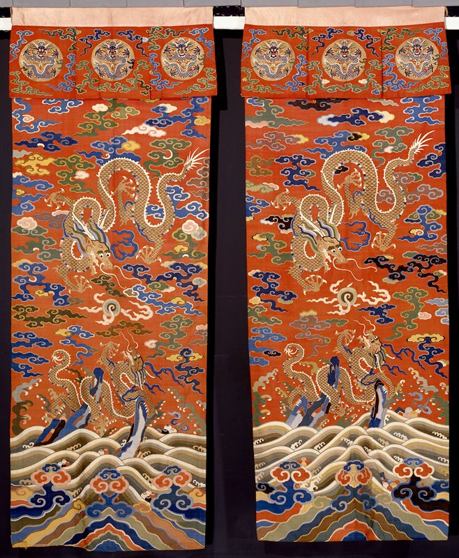 Curtain Hangings, pair of faded lacquer-red k'ossu. Design of two five-clawed dragons in gold in a field of large, loose clouds in shades of blue, green, yellow, brown, peach, pink, and dull gold. Note use of peacock feathers for details in dragons and Heavenly Jewel. At bottom, the Eternal Sea, with wide wavy stripes and deeply rolling waves among which appear cloud heads and symbols of the Eight Precious things. Across the top, a twelve-inch valance on which appear three gold medallions containing five-clawed dragons in blue. Clouds in the surrounding field. Lining and hanging band of faded pink satin of floral medallion design.