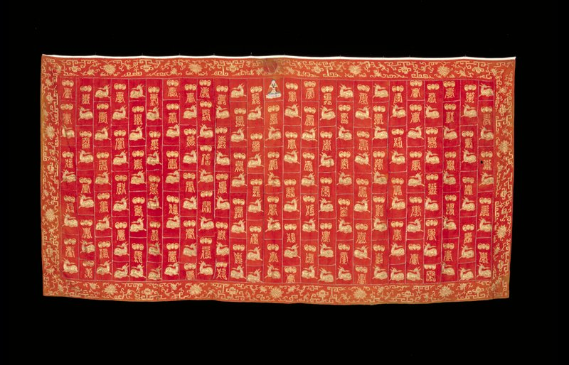 Buddhist priest robe of assembled panels of brocaded red silk, each outlined with gold foil paper, and embroidered in couched gold threads with spotted deer,bats and good luck characters. In the upper center, a seated figure of Buddha embroidered in satin stitch in colored silks. Border embroidered with lotus and greek key motifs in couched gold thread. Soiled and faded. Liningthin flame-red silk.