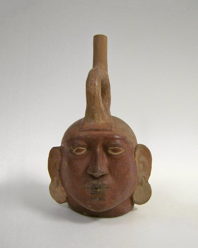 Large portrait head jar with stirrup handle. The face is powerfully modelled with full lips, straight nose, and strongly marked eye sockets. Disk earrings hang from pierced ear lobes. The face of the figure, with the exception of a thin line outlining the eye-socket, is painted brick red. The remainder of the jar is the pale terra cotta color of the body clay. Spout of handle restored.