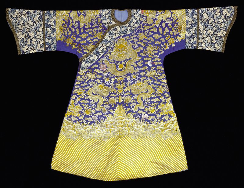Imperial 12-symbol robe of dark blue gauze embroiderd in petit point in shades of yellow and white. Nine 5-clawed dragons, tight clouds, bats, peonies and Taoist symbols. Conventional border of slightly wavy slanting stripes; tight clouds; rolling waves in which appear branches of coral and symbols of the Eight Precious Things. Below border on sleeve- in which appears the endless knot of Buddhism, wide deep cuffs of blue silk embroidered in satin stitch with an all-over design of narcissus blossoms in blue, peach and ivory. Edging of black and gold brocade. Collar band of the same. Note that the 12 ancient symbols have been embroidered in colors, in satin stitch, over the blue and yellow ground. A later addition, this has the look of a bastard. Robe slit at sides and lined with thin blue silk.
