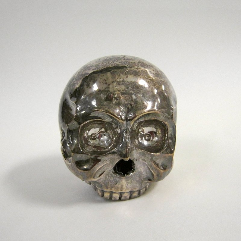 Skull, heavy, hammered and soldered silver work. A solder line bisects the skull vertically, parallel to the face. The incised lines representing sutures are independent of the solder line. Insets in the eye-sockets were once filled with inlaid stones or shells.