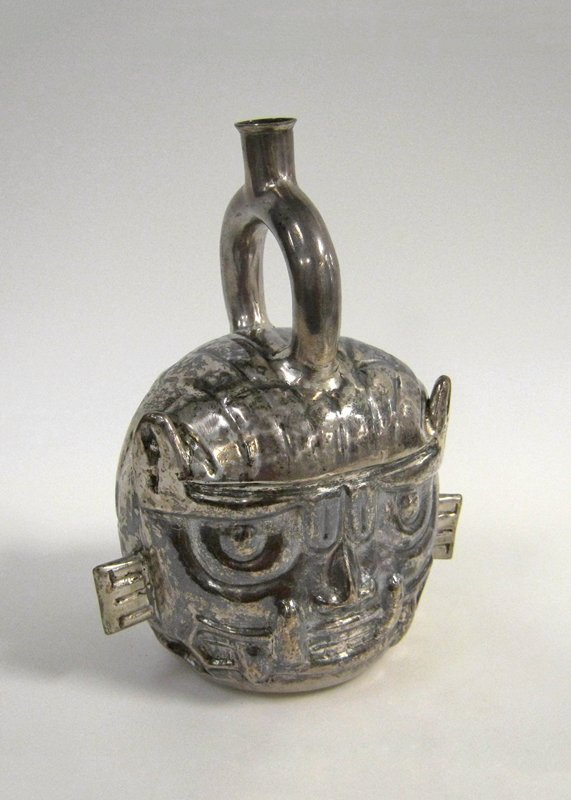 Portrait Jar with Stirrup Spout representing Jaguar God, silver, Peruvian, V-VIc cat. card dims H 9-5/8 inches. Curving eyebrows flare at the ends into cat's ears; bared teeth with four huge tusks protruding. Hammered and soldered, with a horizontal solder line visible around back of head and along upper part of eyebrow groove.