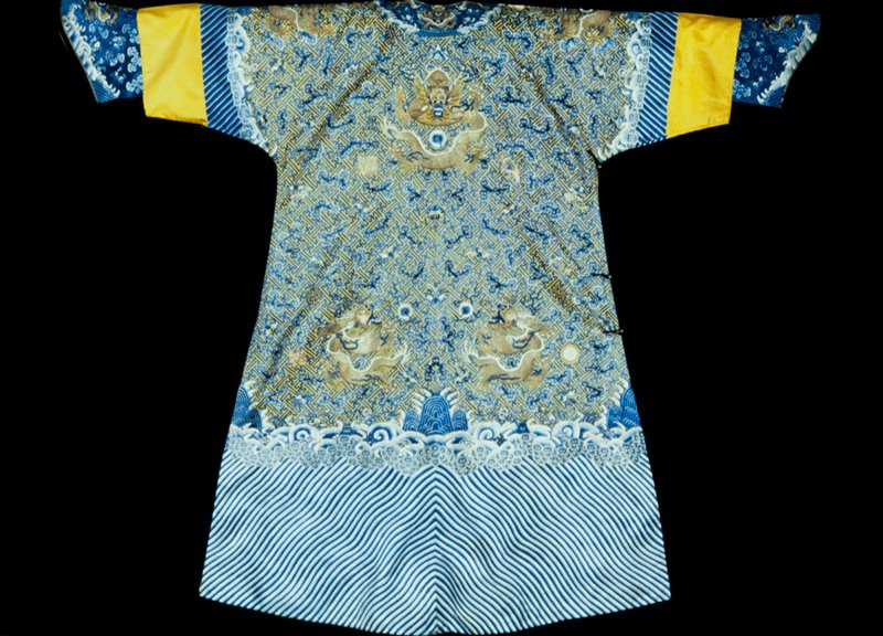 Imperial 12-symbol robe of yellow twilled silk embroidered, save for the nine 5-clawed dragons (couched gold thread) and certain of the 12 symbols, entriely in shades of blue with touches of white. The ground of the sky area is covered with a swastika fret diaper on which appear sprawling, white-eyed clouds, the 12-symbols, bats carrying swastikas, jui scepters, etc, and good luck characters. Border of unusually narrow slanting wavy stripes topped by a narrow strip of clouds tightly massed, and a double row of billows in which appear the Buddhist symbols and Precious Things. Note the unusual treatment of the wine cups. Robe slit at sides and lined with yellow damask with double jui medallions. Band and cuffs of blue-black satin embroidered in blue and gold.