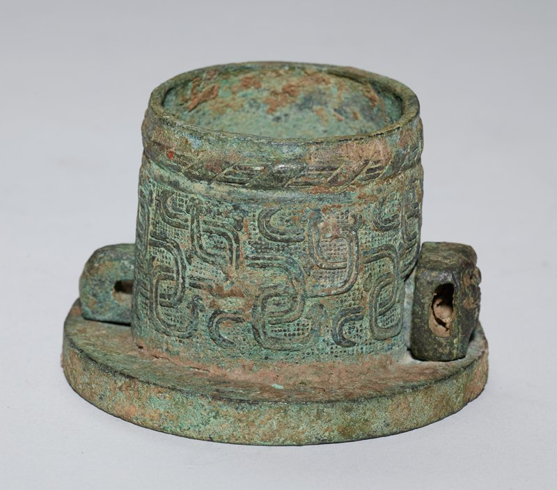 The decor is of entwined serpents on a granulated ground. The outer rim is adorned with a band of raised string pattern bound at intervals with plain, slanting bands. A feline mask appears at the end of the lynch pin, which is pierced at both ends for the passage of a lashing for the pin. Patina bright green.
