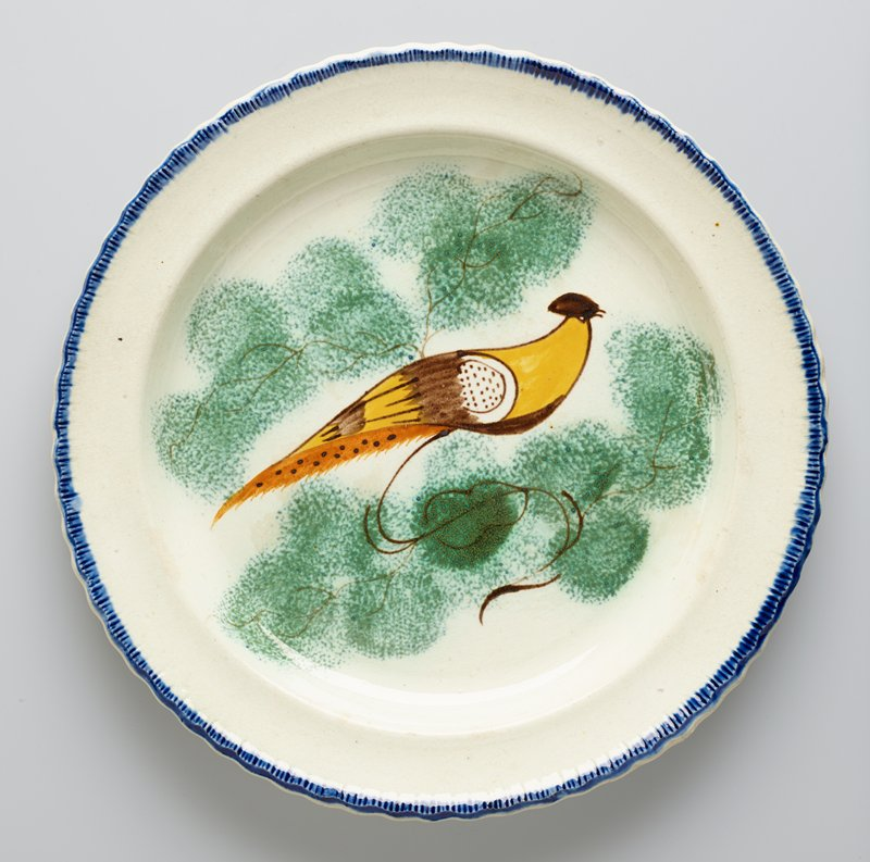 Plate, ceramic-porcelain, decorated with yellow bird in center, narrow blue band around edge; previously catalogued as one of a pair