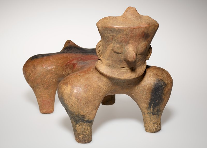 Four-legged figure with human face and tail. Has red band around the middle and black on the back by figures tail.