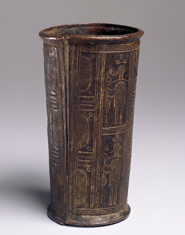 slightly tapering cylindrical shape; decorated with incised geometric designs and 4 stylized human figures with title staffs