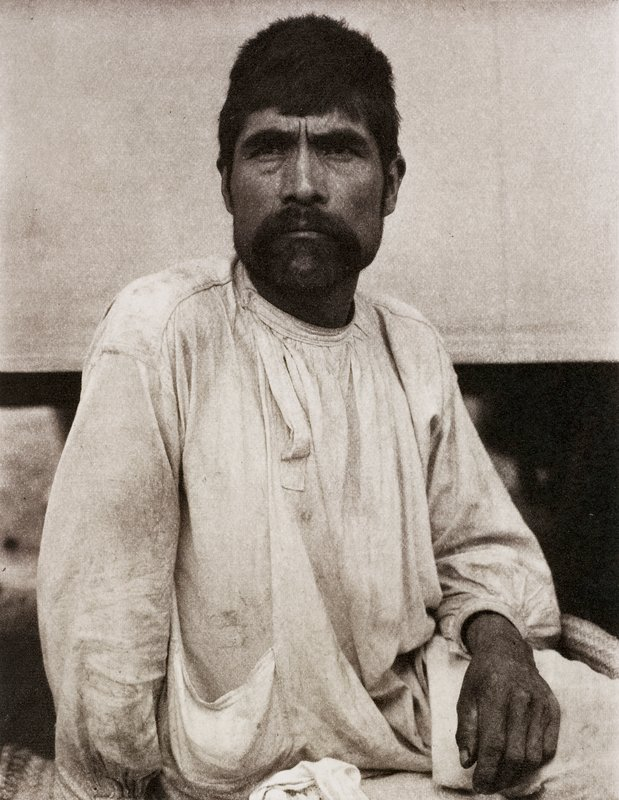 man with dark hair, mustache and beard in light colored loose-fitting garment