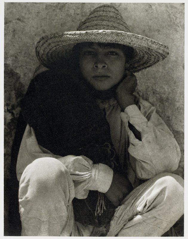 young boy squatting, wearing large hat and serape over p.r. shoulder