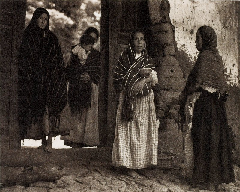 four women standing: two in doorway, two holding babies, three with heads covered.