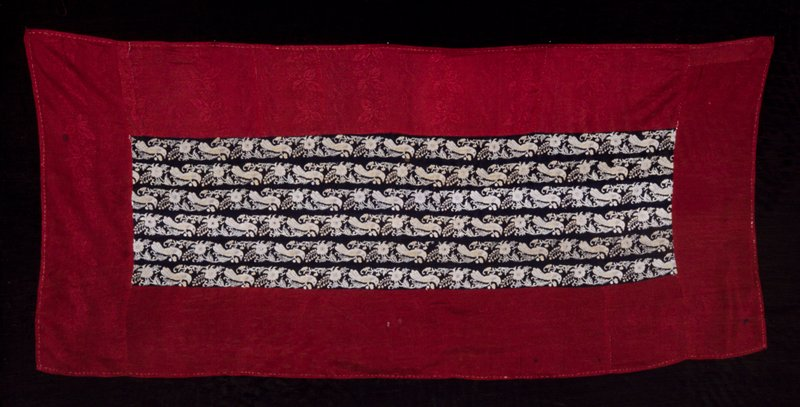 six narrow strips of black silk sewn together onto a piece of wide red brocaded silk; black strips embellished with repeated motif of birds and flowers couched in grey silk thread.