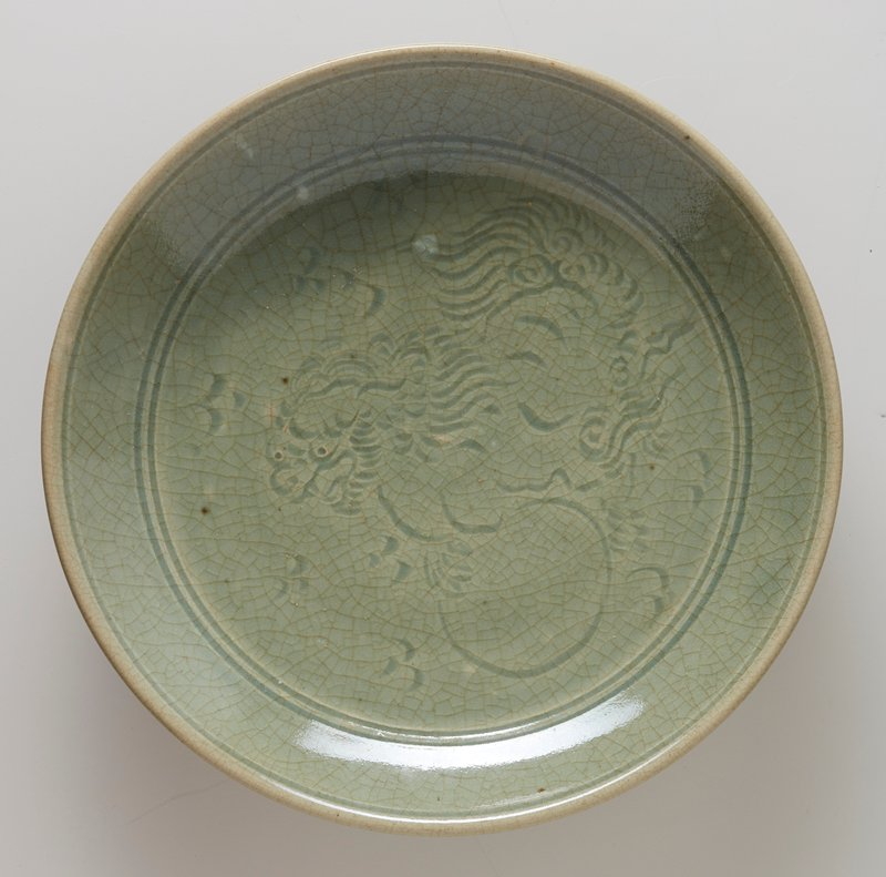 plate, footed, with incised design of foo dog at center and lotus petal motif circling foot; celadon, ceramic, maker Hsien Lu
