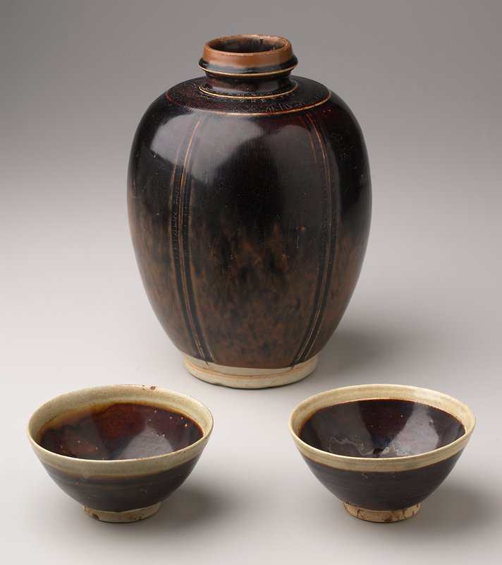 ovoid-shape with vertical incised lines; angled neck with persimmon glaze with streaks on bottom half; dark red glaze on body; unglazed foot